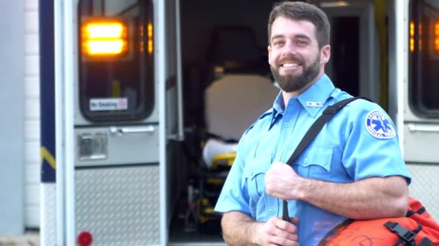 sanitäter steht vor krankenwagen - held stock-videos und b-roll-filmmaterial