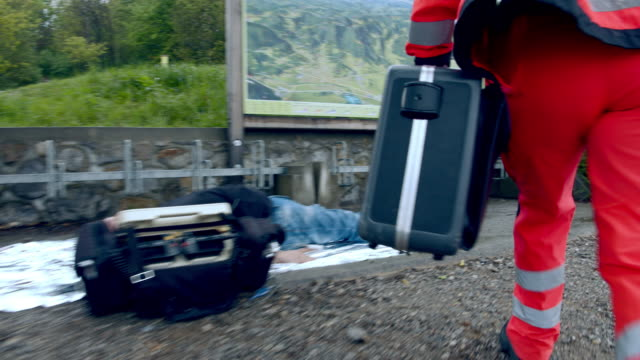 WS Paramedic team attempts to resuscitate the victim Wide shot of a paramedic team attempts to resuscitate the victim lying on the ground on the roadside. defibrillator stock videos & royalty-free footage