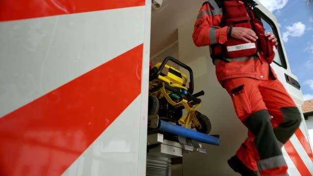 vídeos y material grabado en eventos de stock de equipo slo mo paramédico corriendo fuera de la ambulancia a la escena del accidente - técnico en urgencias médicas