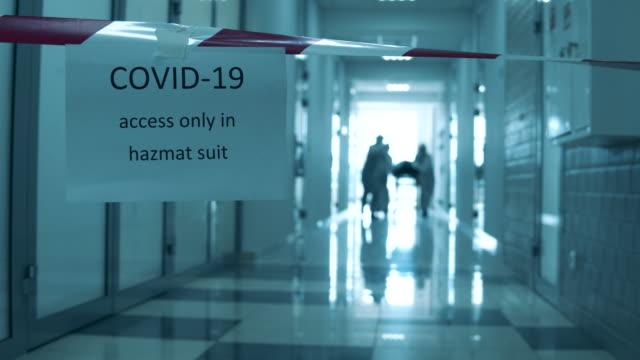 ambulanspersonal transporterar en patient längs hallen i häktet. covid-19 koncept. - intensivvårdsavdelning bildbanksvideor och videomaterial från bakom kulisserna