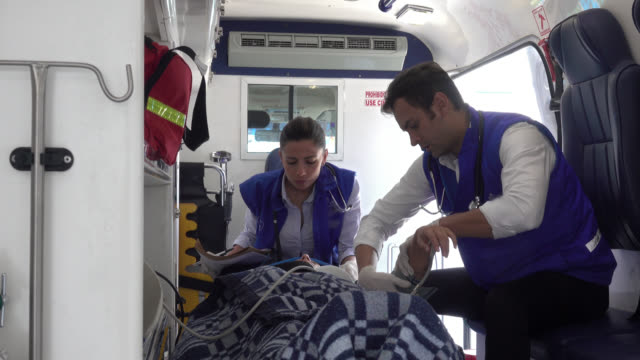 Paramedics attending an unconscious patient Paramedics hurrying to take the vital signs of an unconscious patient lying on a emergency gurney in the ambulance hospital gurney stock videos & royalty-free footage