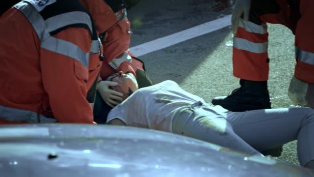 ambulanspersonal kontrollera vitala tecken på en skadad ung kvinna på scenen i en bilolycka - 30 39 år bildbanksvideor och videomaterial från bakom kulisserna