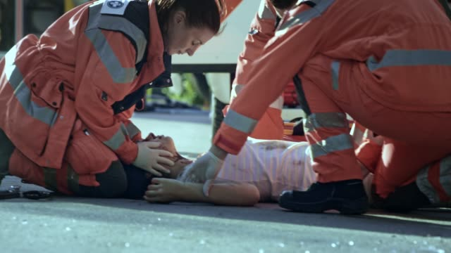 paramedics declaring death of a young woman lying injured on the ground at the scene of a car accident - paramedic stock videos and b-roll footage