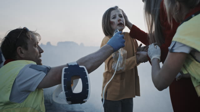 Paramedics Giving First Aid Oxygen Mask to a Young Girl Victim of the Accident. Professionals Saving Lives. Smoke Everywhere Paramedics Giving First Aid Oxygen Mask to a Young Girl Victim of the Accident. Professionals Saving Lives. Smoke Everywhere rescue worker stock videos & royalty-free footage