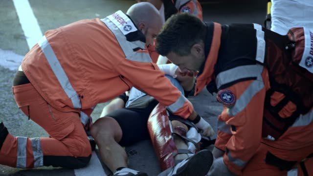 paramedics immobilizing the injured cyclist's leg on the stretcher - paramedic stock videos and b-roll footage