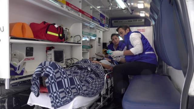 Paramedics in an ambulance with a patient Paramedics in the ambulance taking vital signs of a patient lying on an emergency gurney unconscious stretcher stock videos & royalty-free footage