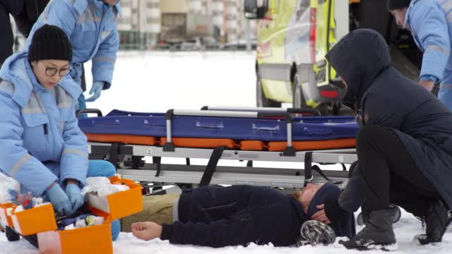 paramedics lifting man on stretcher - first responders filmów i materiałów b-roll