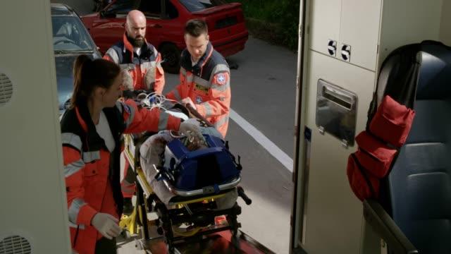 ローディングの救急車に自動車事故でけがをした人を救急隊員 ビデオ