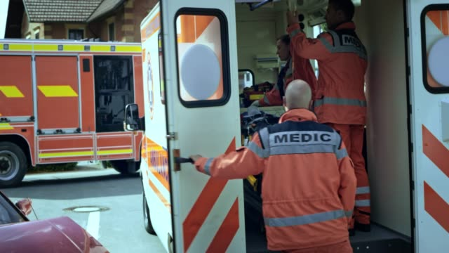 Paramedics loading the injured person into the ambulance and closing the door Wide handheld shot of the paramedic team loading an injured person on the stretcher into the ambulance and closing the door. Shot in Slovenia. stretcher stock videos & royalty-free footage