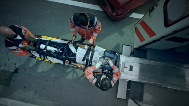 CS Paramedics loading the injured woman on the stretcher into the ambulance Wide crane shot of the paramedic team securing the straps and loading an injured woman on the stretcher into the ambulance. Shot in Slovenia. mid adult stock videos & royalty-free footage