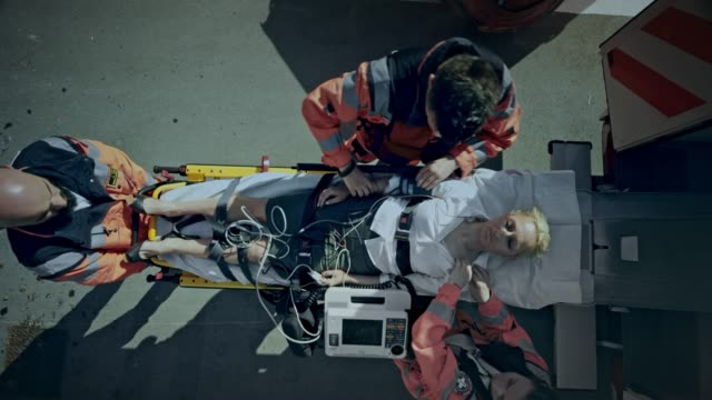 CS Paramedics preparing the injured woman on the stretcher for transport and loading her into the ambulance Wide crane shot of the paramedic team securing the straps on the stretcher and preparing the injured woman for transport. They load her into the ambulance. Shot in Slovenia. stretcher stock videos & royalty-free footage