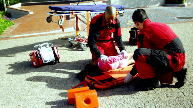 Paramedics putting injured girl onto a backboard Paramedics putting injured girl onto a backboard on street stretcher stock videos & royalty-free footage