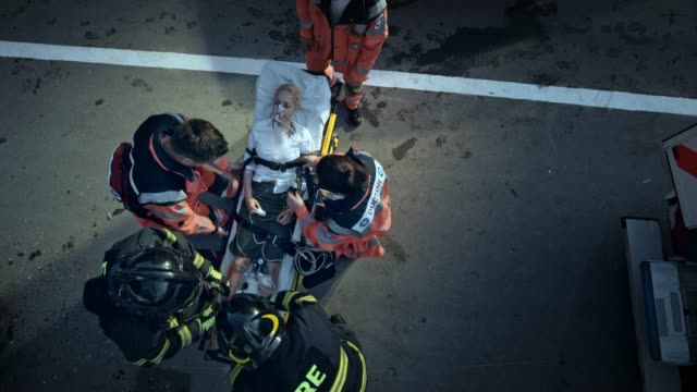 cs paramedics securing the injured woman on the stretcher for transport with the help of the firemen - evento catastrofico video stock e b–roll