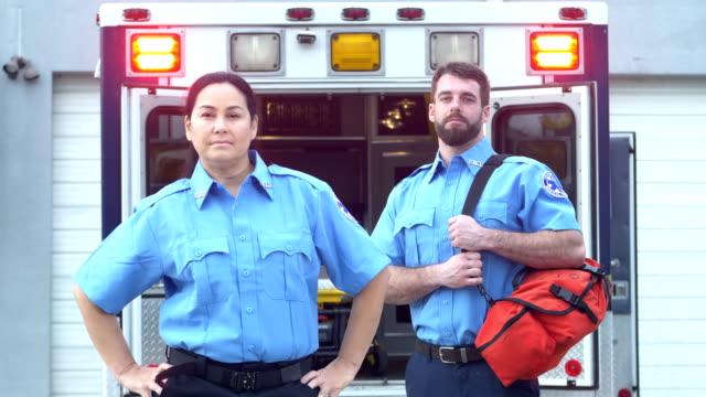 ambulansın önünde duran sağlık görevlileri - first responders stok videoları ve detay görüntü çekimi