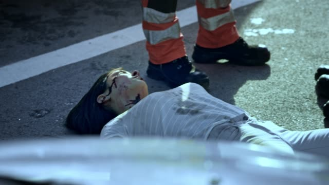 paramedics taking a moment to process the death of a young woman at the scene of a car accident - cadavere video stock e b–roll