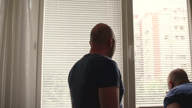 Paranoid man looking through the window video