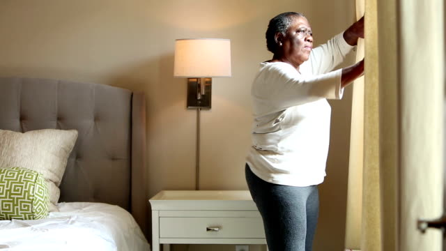 Paranoid senior woman in bedroom looks out window