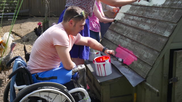 Paraplegic Helping to Paint Chicken Shed A group of people helping to paint a chicken coop in the middle of their local farm. disability stock videos & royalty-free footage