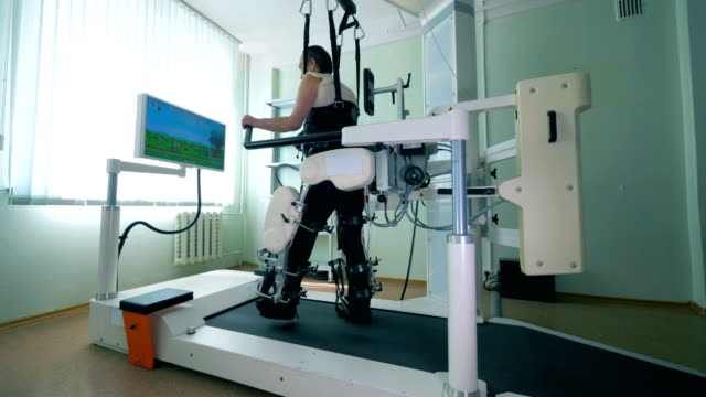 Paraplegic patient is practicing walking on a special simulator. Virtual reality simulator for patient rehab. Paraplegic patient is practicing walking on a special simulator. 4K prosthetic equipment stock videos & royalty-free footage