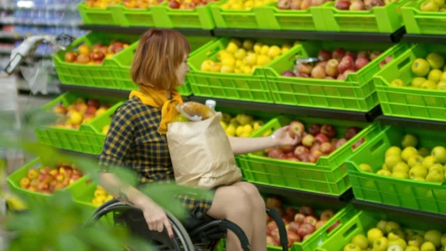 Paraplegic Woman Choosing Apples in Grocery Store video