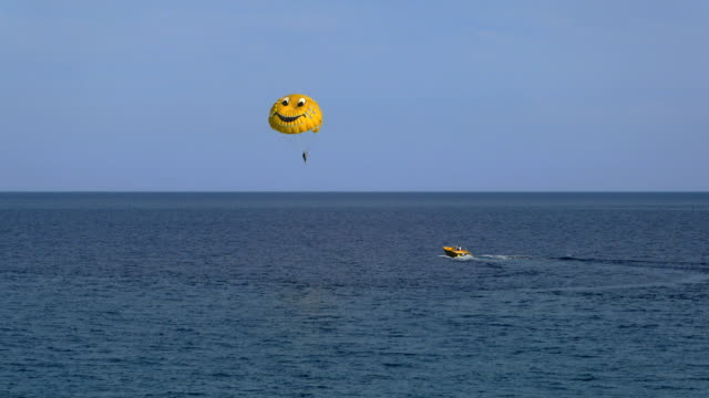 parasailing by boat at Mediterranean sea in daytime, sunny weather video