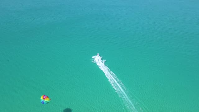 parasailing in blue sea drone view. parasailing summer activity and extreme entertainment while resting on resort beach. colorful parasail wing pulled by sea boat in the sea water aerial view - парапланеризм стоковые видео и кадры b-roll