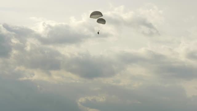 Paratrooper landing with two parachutes - slowmotion 60fps video