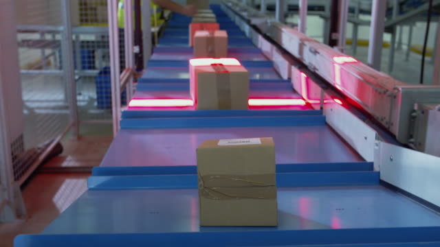 parcels are moving on belt conveyor at post sorting office. box pov. time-lapse. - automatico video stock e b–roll
