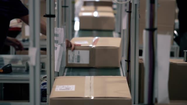 vídeos de stock, filmes e b-roll de as encomendas em uma caixa de papelão se movem ao longo da linha de embalagem em um armazém. as parcelas se movem sozinhas na esteira. automação da logística de transporte online - frete