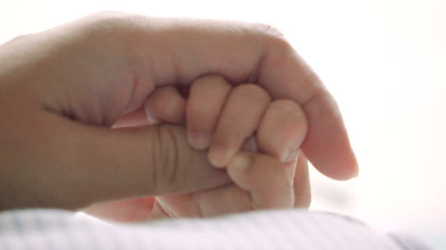 Parent holding newborns hand video