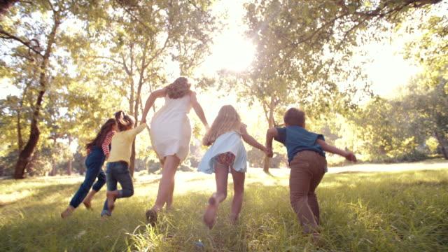 stockvideo's en b-roll-footage met parent running with kids through a sunlit park - parkeren