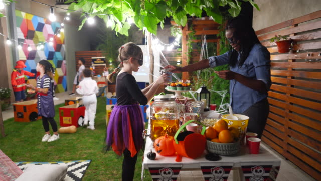 Parent serving candy and popcorn to her kids and their friends at backyard movie night Parent serving candy and popcorn to her kids and their friends at backyard movie night halloween covid stock videos & royalty-free footage