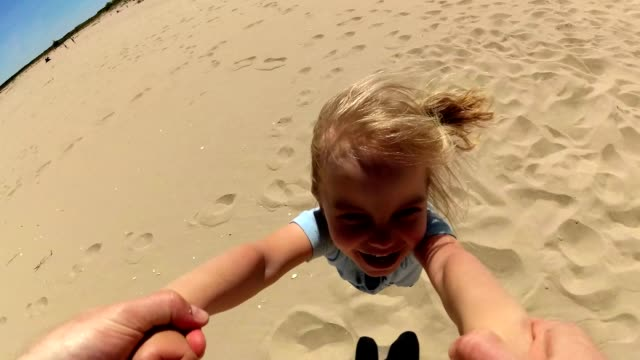 Parent Spinning Daughter By Hands On Beach POV