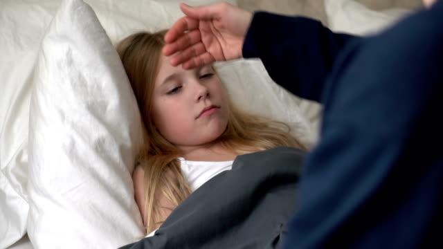 vídeos de stock e filmes b-roll de mãe tendo o cuidado de uma criança mal - doença