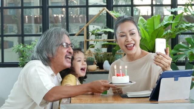 förälder undervisning barn om biologi och sociala avstånd en fest födelsedag av smartphone växthus hemma, ny normal livsstil, hemundervisning koncept - birthday celebration looking at phone children bildbanksvideor och videomaterial från bakom kulisserna