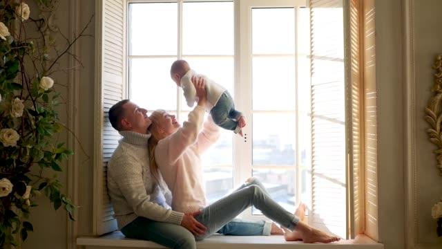 창에 앉아있는 부모와 소년 아이 - happy family 스톡 비디오 및 b-롤 화면