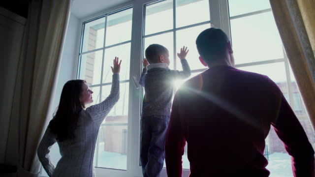 Parents and child looking out the window, the sunlight in the window video