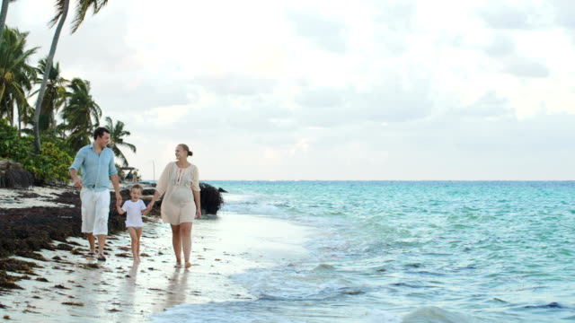 Parents and child walking along the beach holding hands video