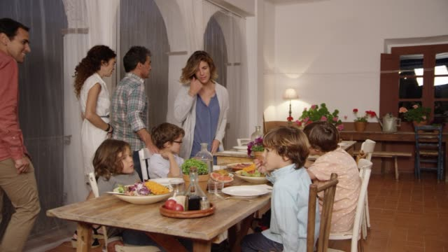 Parents and children having dinner at dining table