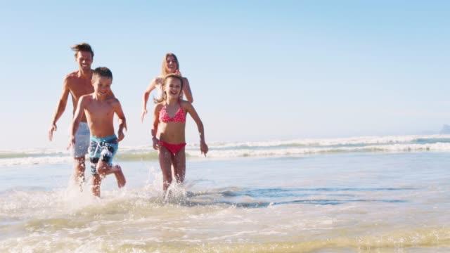 vídeos de stock, filmes e b-roll de pais e filhos em trajes de banho ficando sem mar nas férias de verão - férias na praia
