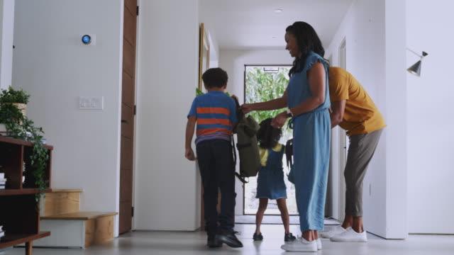 genitori e figli che aprono la porta d'ingresso e e lasciano casa insieme - partire video stock e b–roll