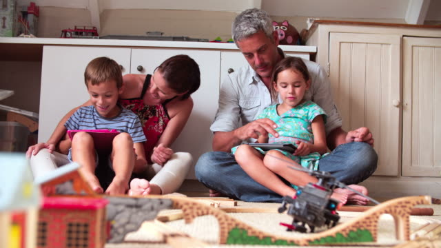 Parents And Children Playing With Digital Tablets In Bedroom video