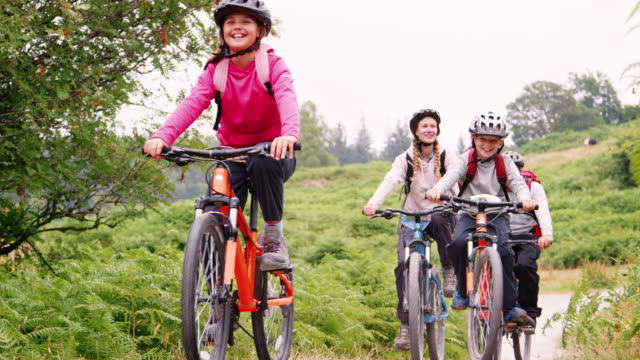 parents and children riding mountain bikes on a country path during a family camping holiday, lake district, uk - montare video stock e b–roll