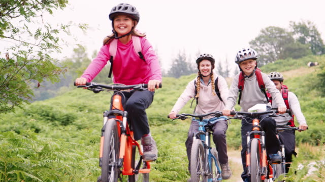 parents and children riding mountain bikes on a path in the countryside during a family camping holiday, lake district, uk - campeggio video stock e b–roll