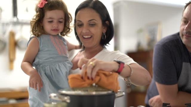 föräldrar och dotter förbereder popcorn hemma - enföräldersfamilj bildbanksvideor och videomaterial från bakom kulisserna