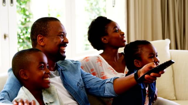 vídeos y material grabado en eventos de stock de padres y niños que se divierten mientras mira la televisión en la sala - family watching tv