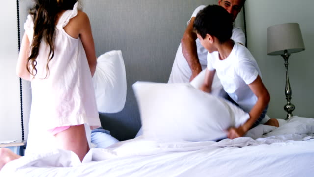 föräldrar och barn att ha kudde slåss på sängen i sovrummet - cosy pillows mother child bildbanksvideor och videomaterial från bakom kulisserna