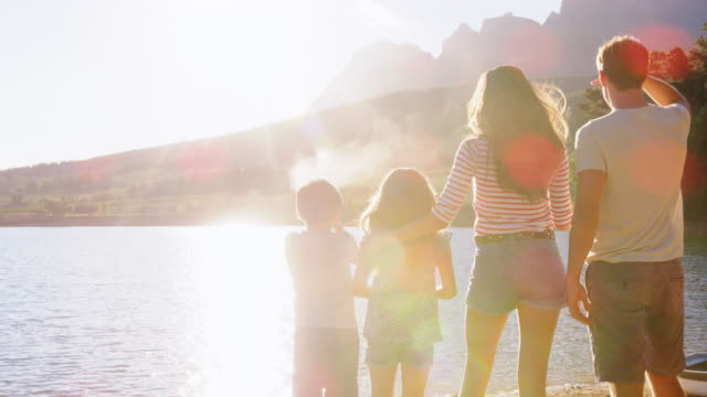 Parents and two kids standing on jetty by lake, back view Parents and two kids standing on jetty by lake, back view jetty stock videos & royalty-free footage