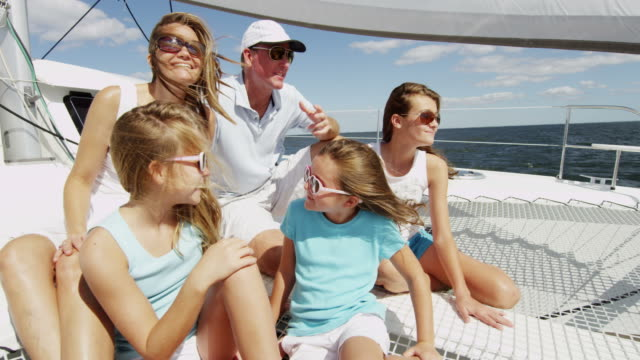 parents and young caucasian sisters sailing ocean catamaran - financial planning stock videos & royalty-free footage