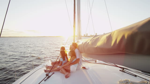 Parents and young Caucasian sisters sailing ocean yacht Happy young Caucasian mother father love smiling girls Caribbean vacation financial planning holiday yacht carefree lifestyle RED EPIC wealth stock videos & royalty-free footage